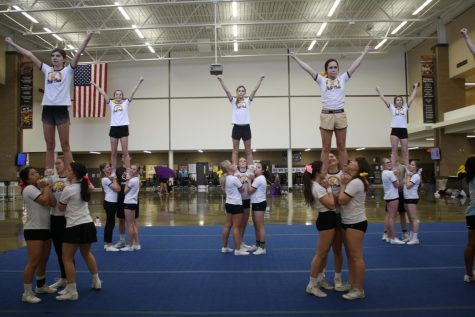 The cheer team practices a stunt commonly done at tryouts.