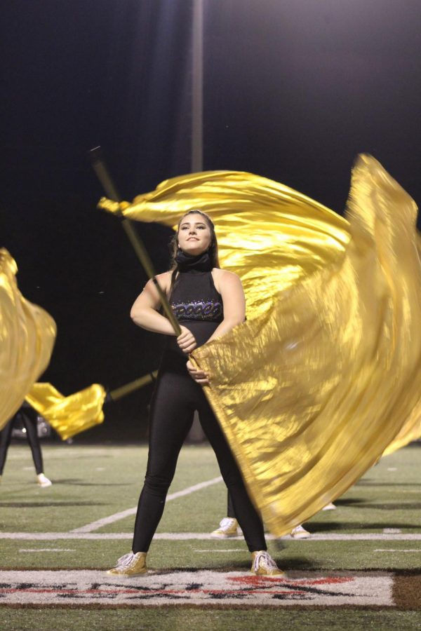 Senior Emily Young performs with the colorguard at an Friday football game. Photo credit to Lauren Arnold.