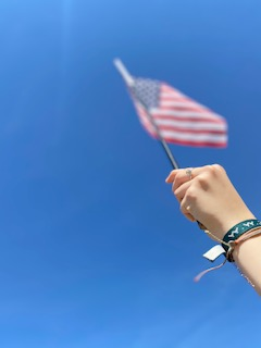 Sophomore, Gabby Burgess, holds an American flag proudly under a scenery of a blue sky.