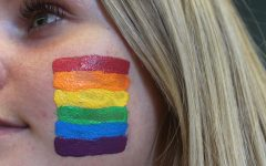 Junior Maggie Miller supporting the LGBTQ+ community by previewing the Pride flag on her cheek.