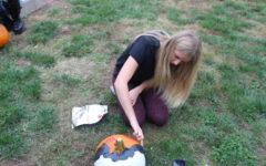 Maggie Miller (12) paints pumpkin.
